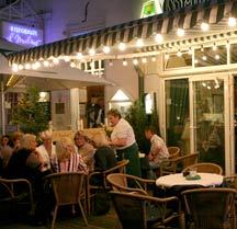 Menschen beim Abendessen auf der beleuchteten Terrasse eines Altstadt-Restaurants.