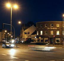 Nachtbild der Verkehrskreuzung vor dem Restaurant 'Zur Trotzburg' mit vorbeifahrenden Autos.